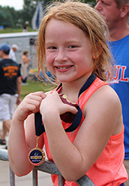 Girl with medal at Run with Carl